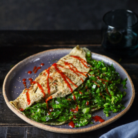 Baby greens omelette with garlic and chilli sauce